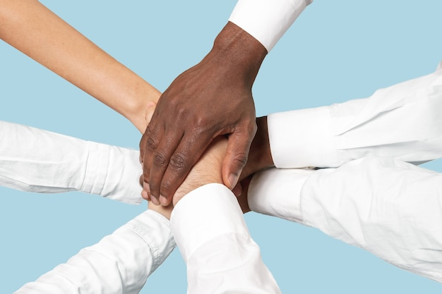 Praca zespołowa i komunikacja. mężczyzna i kobieta trzymając się za ręce na białym tle na niebieskim tle.