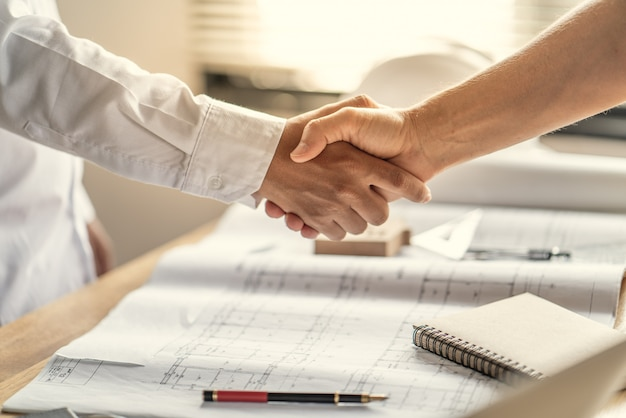 Praca zespołowa jest szczęśliwa i podają sobie ręce, aby świętować sukces w planowaniu pracy o projekt budowy domu