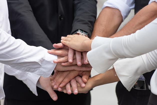 Praca zespołowa ludzi biznesu składa ręce.