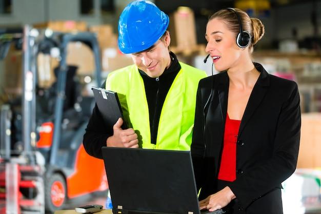 Praca zespołowa, magazynier lub kierowca wózka widłowego i przełożona z laptopem, zestawem słuchawkowym i telefonem komórkowym, w magazynie firmy spedycyjnej wózek widłowy