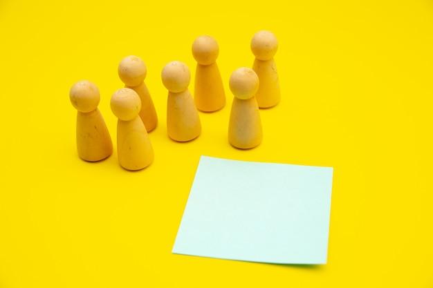 Praca zespołowa, makieta budowania zespołu, struktura firmy. drewniane figurki stoją nad izolowanym żółtym w pobliżu niebieskiej karteczki, miejsce na tekst