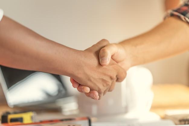 Praca zespołowa oficera jest szczęśliwa i uścisk dłoni, aby świętować sukces w zakończeniu planowania pracy.