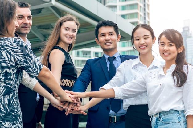 Praca zespołowa partnerów biznesowych łączy ręce.