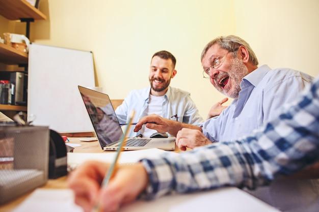 Praca zespołowa. starzy i młodzi człowiecy pracuje z nowym projektem w biurze