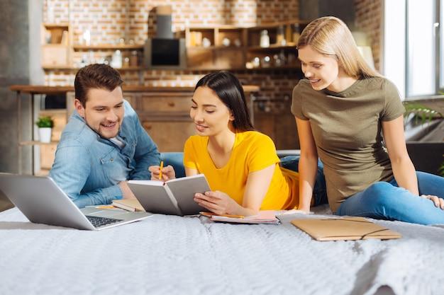 Praca zespołowa. trzech wesołych pozytywnych przyjaciół gejów patrząc na notebooka, uśmiechając się i komunikując się