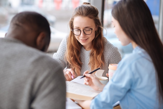 Praca zespołowa. trzej studenci z zagranicy uczą się razem, siedząc w lekkiej kawiarni podczas przerwy obiadowej.