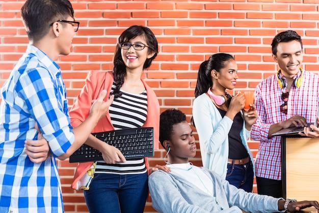 Praca zespołowa w start-upowej przestrzeni coworkingowej przy omawianiu nowych projektów