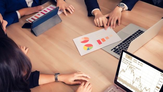 Praca zespołowa z wykresem kosztów analizy ludzi biznesu w sali konferencyjnej