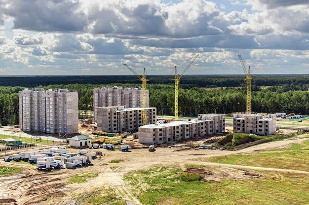 Praca żurawi wieżowych na tle zachodzącego nieba. nowoczesne budownictwo mieszkaniowe. inżynieria przemysłowa. budowa mieszkań hipotecznych.