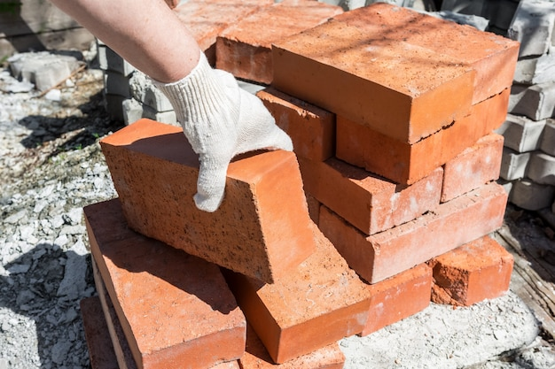 Prace budowlane w prywatnym domu murarz bierze cegły ze stosu