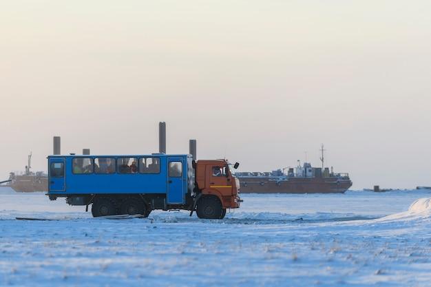 Prace budowlane w zimowej tundrze. specjalny autobus z ludźmi. budowa zapory, dźwig, barka, pogłębiarka.