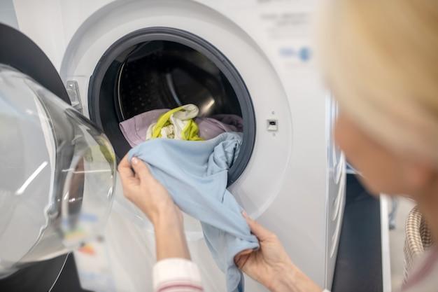 Prace domowe. kobieta gospodyni wkłada ubrania do pralki