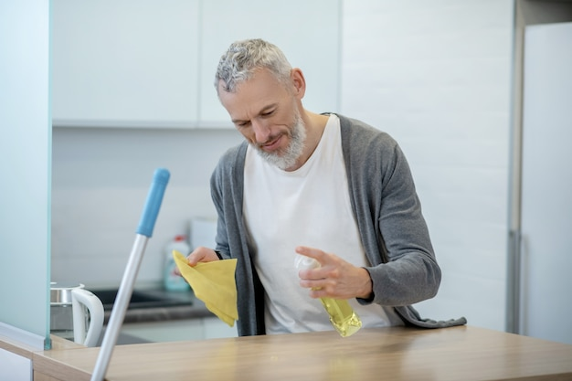 Prace domowe. mężczyzna w stroju domowym robi prace domowe i wygląda na zajętego
