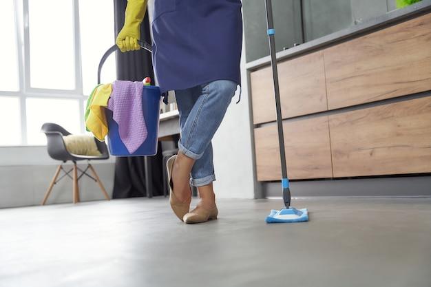 Prace domowe przycięte zdjęcie kobiety trzymającej mop i plastikowe wiadro lub kosz ze szmatami