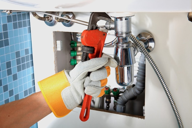 Prace hydrauliczne i sanitarne przy naprawie rury pod zlewem. prace sanitarne. naprawa hydraulika