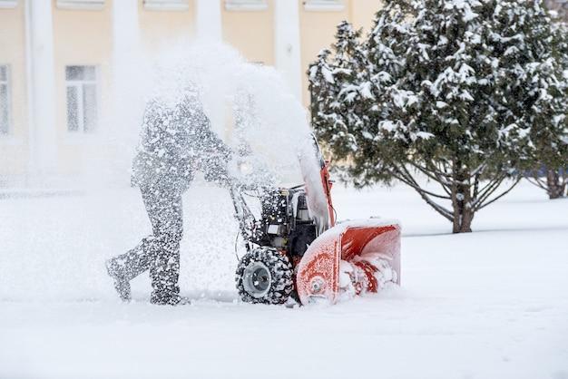 Prace odśnieżające za pomocą dmuchawy do śniegu. człowiek usuwanie śniegu. silne opady i hałdy śniegu