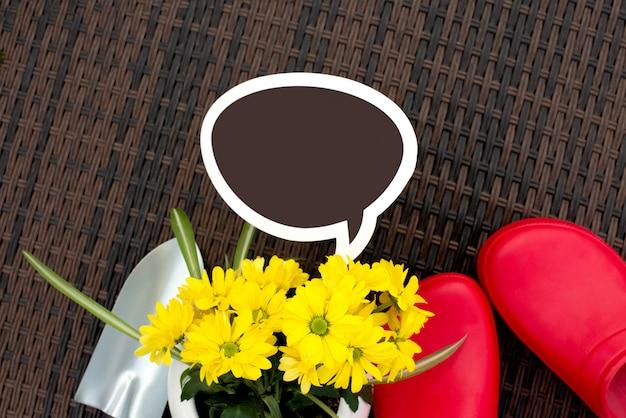 Prace ogrodowe. jesienna praca w ogrodzie. narzędzia, konewka i kwiat w doniczce na tle wiklinowego rattanu. czarna tablica kredowa do napisów.