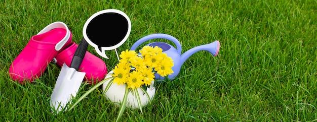 Prace ogrodowe. praca w ogrodzie. narzędzia, konewka i kwiat w doniczce na tle zielonych liści.