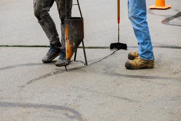 Prace renowacyjne polegające na nałożeniu ciekłego środka uszczelniającego na asfalt i warstwę ochronną drogi na uszczelnienie pęknięć jezdni