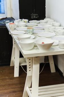 Prace w toku stoją w domowej pracowni ceramiki artystów. naczynia kamionkowe wysuszone i gotowe do palenia.
