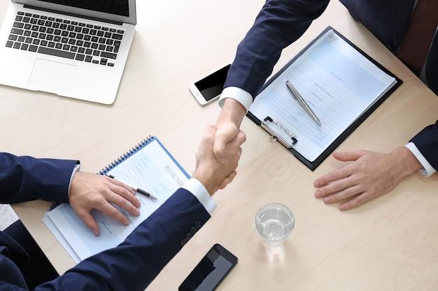 Pracodawca i kandydat ściskają sobie dłonie po rozmowie kwalifikacyjnej