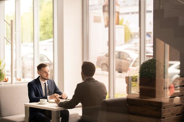 Pracodawca i kandydat w formalnym stroju rozmawiają o warunkach pracy siedząc naprzeciwko siebie przy stoliku w kawiarni