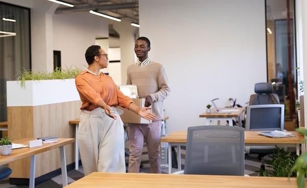 Pracodawca pokazuje człowiekowi swoje biurko w nowej pracy, niosąc pudełko z rzeczami