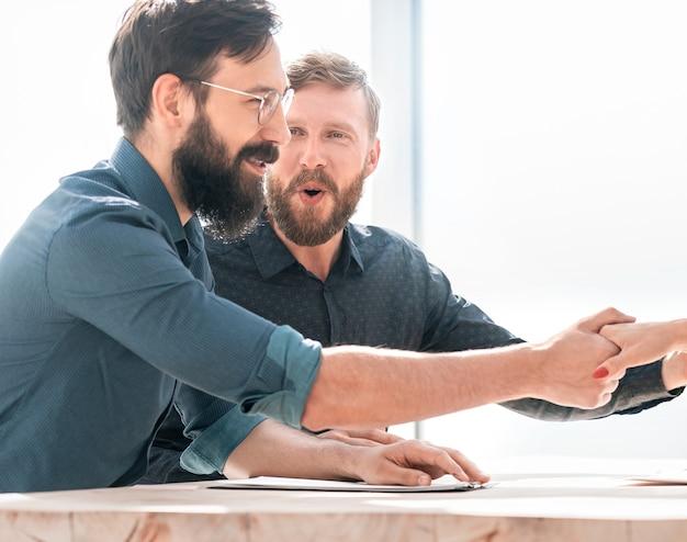 Pracodawca uścisnął dłoń nowemu pracownikowi podczas rozmowy kwalifikacyjnej. koncepcja współpracy