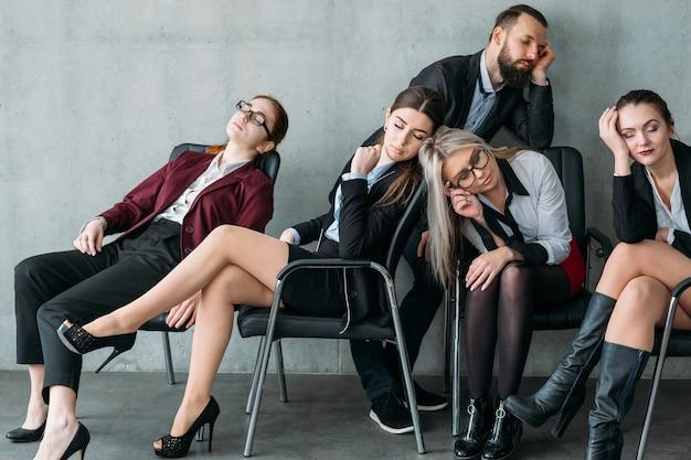 Pracoholicy korporacyjni. przepracowanie. członkowie zespołu firmy spanie na krzesłach w miejscu pracy.