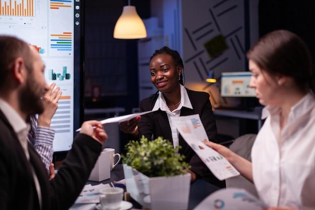 Pracoholicy skoncentrowani na wieloetnicznych biznesmenach przepracowujących się w firmowej sali konferencyjnej podczas burzy mózgów późno w nocy