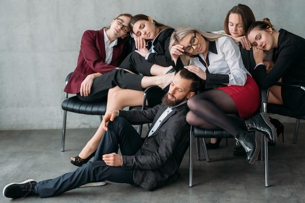 Pracoholicy zarabiający pieniądze. okres księgowy. przepracowane samice śpiące na krzesłach z mężczyzną na podłodze.