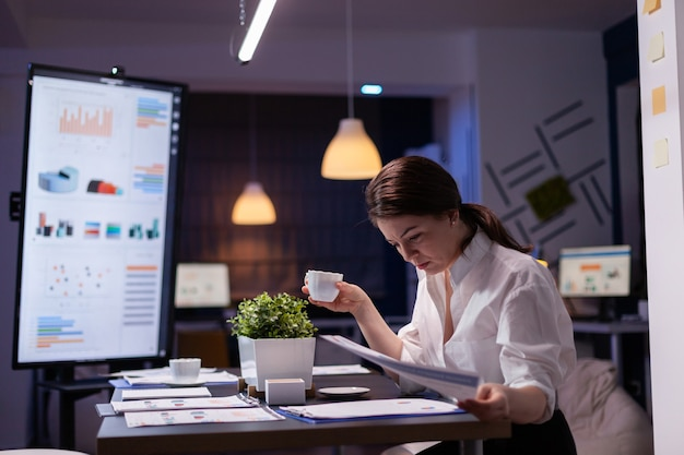 Pracoholik businesswoman patrząc na prezentację raportów na monitorze w porównaniu z wykresem finansowym na papierkowej robocie. skoncentrowany menedżer pracujący w biurze spotkań firmy biznesowej późno w nocy