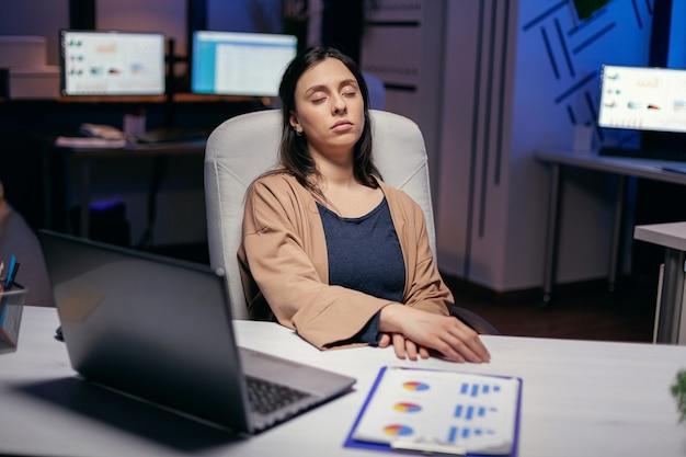 Pracoholik freelancer śpiący w pustym biurze w trakcie realizacji projektu terminowego. pracownik zasypiający samotnie do późnych godzin nocnych w biurze dla ważnego projektu firmy.