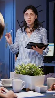 Pracoholik skoncentrowany bizneswoman wyjaśniający rozwiązanie do zarządzania wskazujące strategię na monitorze