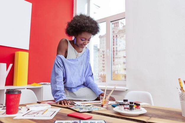 Pracować ciężko. młody stylowy piękny artysta na sobie sukienkę w paski i niebieską koszulę ciężko pracuje