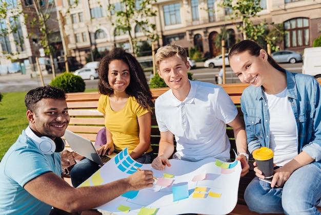 Pracować razem. zachwyceni młodzi ludzie siedzący na ławce i wyrażający pozytywne nastawienie, patrząc w przyszłość