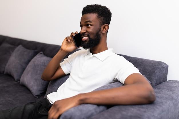 Pracować w domu. szczęśliwy człowiek afrykański rozmawia przez telefon komórkowy sittin na kanapie w domu