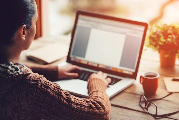 Pracować w domu. zbliżenie: młoda kobieta pracuje na laptopie, siedząc przy szorstkim drewnianym stole