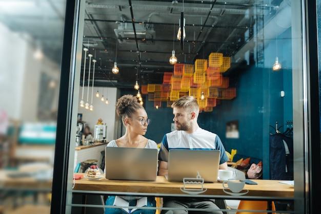 Pracowici freelancerzy. przystojni, ciężko pracujący freelancerzy ciężko pracują, siedząc w przyjemnej stołówce