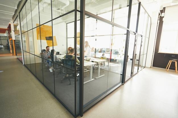 Pracowici młodzi ludzie pracujący w przytulnym, nowoczesnym biurze ze szkła