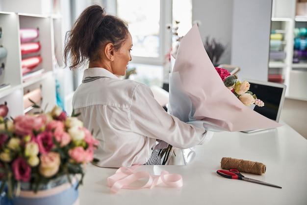 Pracowita kobieta niosąca gotową kompozycję kwiatową w kwiaciarni