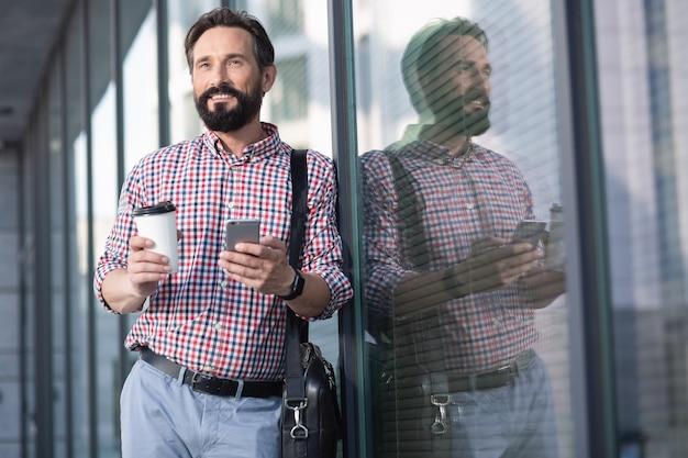 Pracowite dni. w pasie przyjemny brodaty mężczyzna pije kawę, stojąc w pobliżu biurowca