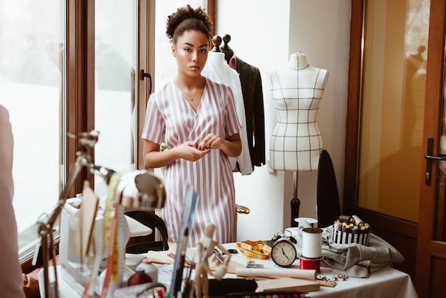 Pracowity, kreatywny krawiec. młoda afrykańska kobieta, w pobliżu stołu roboczego z różnymi przedmiotami rzemieślniczymi. stoi w pobliżu manekina sukni