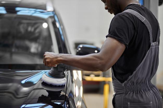 Pracowity mechanik samochodowy polerujący samochód w serwisie samochodowym