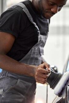 Pracowity mechanik samochodowy poleruje samochód przy użyciu specjalnego sprzętu