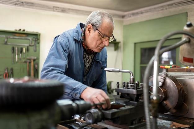 Pracowity mężczyzna wykonujący swoją pracę w warsztacie przemysłowym