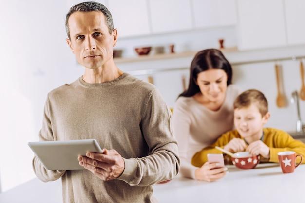 Pracowity poranek. skupiono się na poważnym młodym mężczyźnie trzymającym tablet, podczas gdy jego żona i syn oglądają coś przez telefon i jedzą śniadanie