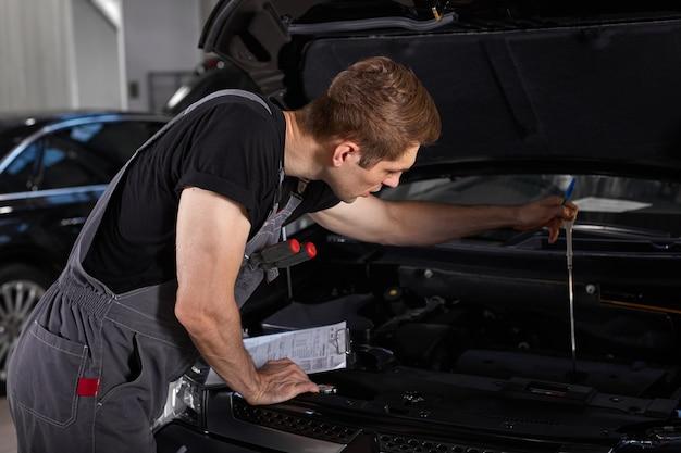 Pracowity pracownik facet w mundurze pracuje w salonie samochodowym