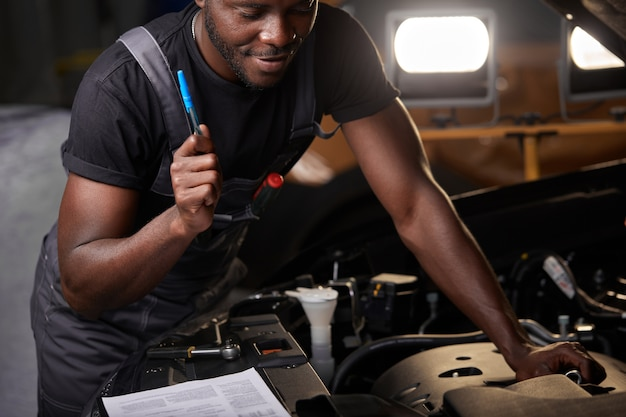 Pracowity pracownik w mundurze pracuje w salonie samochodowym