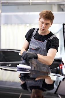 Pracowity pracownik w mundurze pracuje w serwisie samochodowym